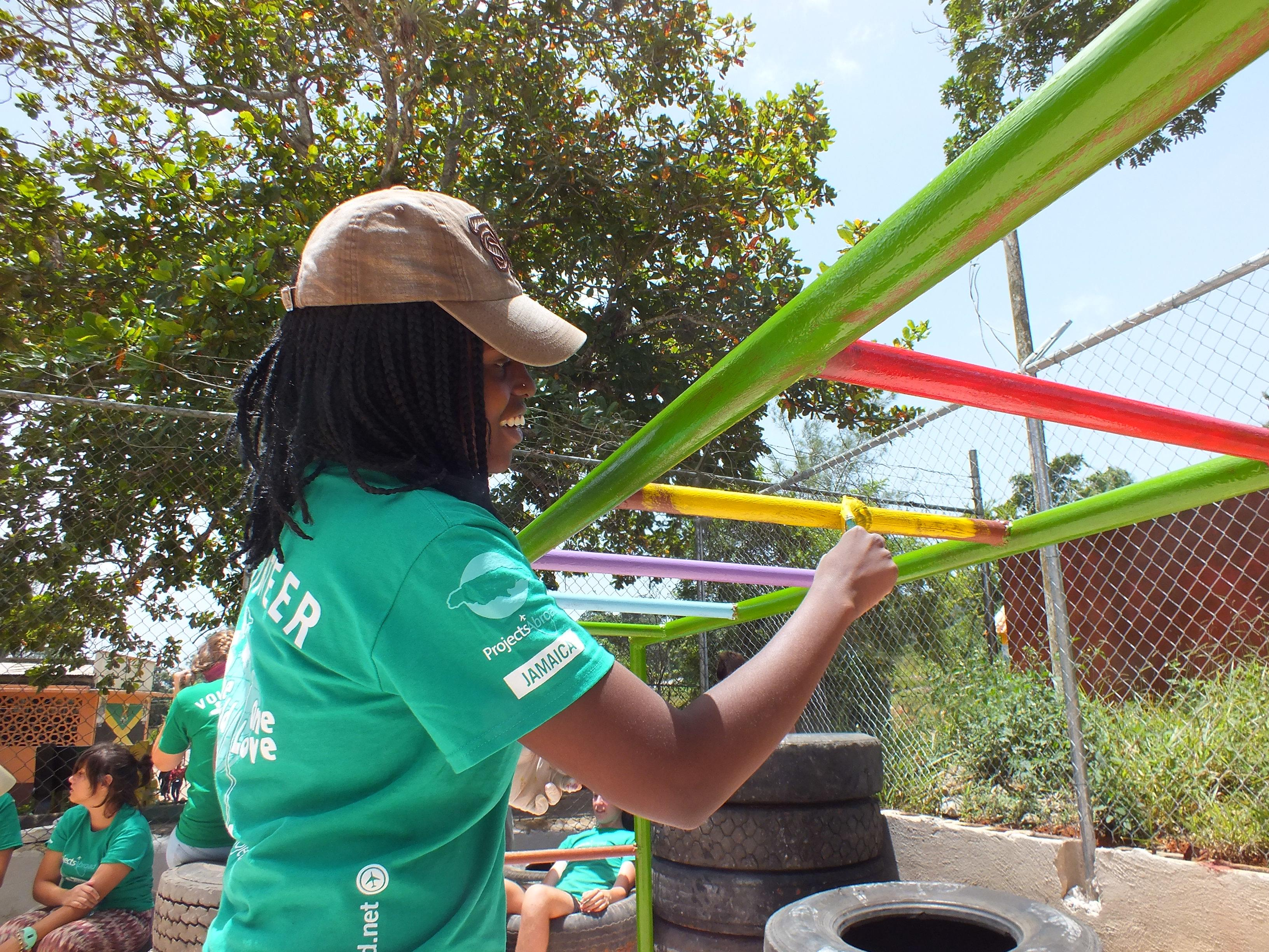 A female Projects Abroad volunteer helps refurbish playground equipment in Jamaica as part of her summer volunteer abroad program.
